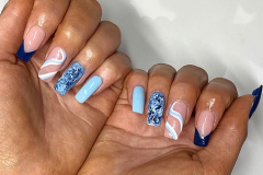 Quick Tip nail extensions with blue design.